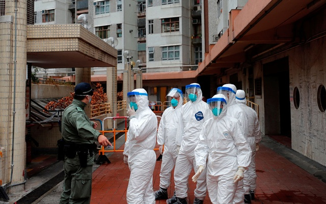 Police in protective gear wait to evacuate residents from a public housing building, following the outbreak of the novel coronavirus, in Hong Kong, China Feb 11, 2020. REUTERS