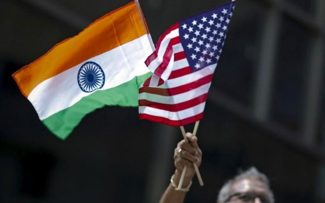 FILE PHOTO: A man holds the flags of India and the US while people take part in the 35th India Day Parade in New York Aug 16, 2015. REUTERS