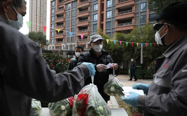 Community workers distribute free vegetables to members of households inside the residential compound, following the outbreak of the novel coronavirus in Wuhan, Hubei province, China February 11, 2020. China Daily via REUTERS
