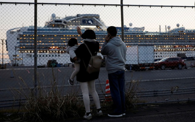 Family members of passengers onboard the cruise ship Diamond Princess, where dozens of passengers were tested positive for coronavirus, wave and talk to them on the phone at Daikoku Pier Cruise Terminal in Yokohama, Japan February 11, 2020. Reuters