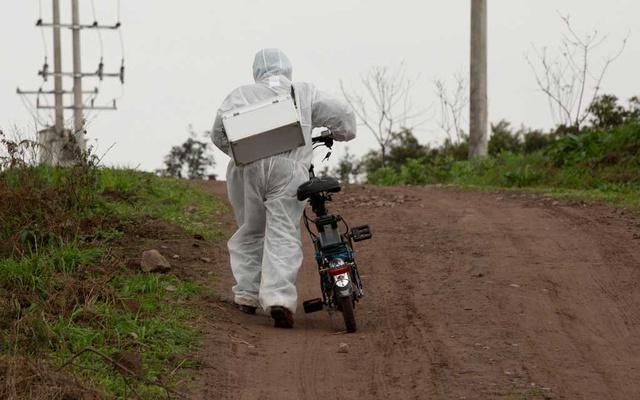 A medical worker in protective suit pushes his electric bicycle up a hill as he visits villagers for body temperature measurements, following an outbreak of the novel coronavirus in the country, at a village in Luzhou, Sichuan province, China Feb 10, 2020. REUTERS