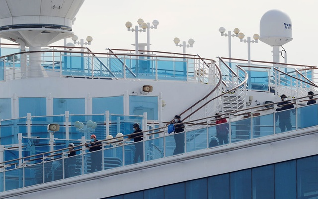 Passengers look out from a deck of the cruise ship Diamond Princess at Daikoku Pier Cruise Terminal in Yokohama, south of Tokyo, Japan Feb 12, 2020. REUTERS