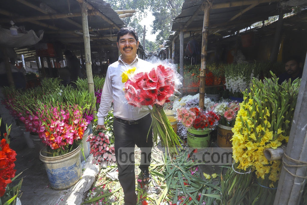 A retailer comes to the Agargaon wholesale market in Dhaka to collect a variety of flowers on Thursday. Photo: Asif Mahmud Ove
