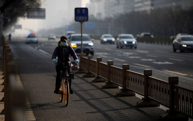 A woman wearing a face mask rides a shared bicycle on a main road in central Beijing in the morning after the extended Lunar New Year holiday caused by the novel coronavirus outbreak, China Feb 10, 2020. REUTERS