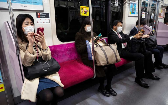 Passengers wearing protective face masks are seen as they ride on a train in Tokyo, Japan, February 14, 2020. REUTERS