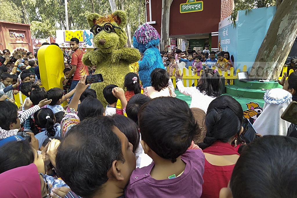 Children with famous characters Ikri and Shiku of TV show Sisimpur at the Amar Ekushey Book Fair in Dhaka on Saturday.