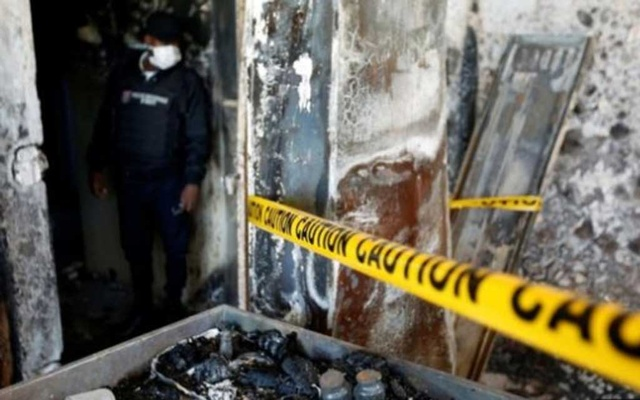 A police officer looks at burnt debris at an orphanage after it was partially destroyed in a fire, in Port-au-Prince, Haiti, February 14, 2020. REUTERS