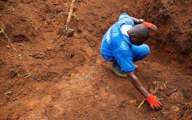 A Burundian worker from the Truth and Reconciliation Commission extracts a body of an unidentified person from a mass grave in the Bukirasazi hill in Karusi Province, Burundi January 27, 2020. Reuters