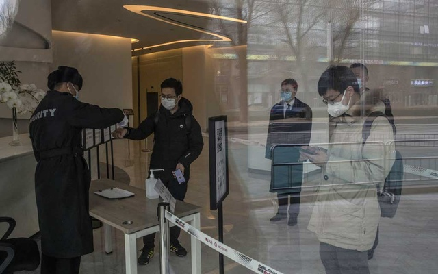 A security worker checks visitors at the entrance of an office building in Beijing on Feb 13, 2020. The New York Times