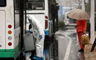 A worker in protective suit lifts a suitcase from a bus amid snow to help transport novel coronavirus patients outside a hospital in Wuhan, Hubei province, China February 15, 2020. China Daily via REUTERS