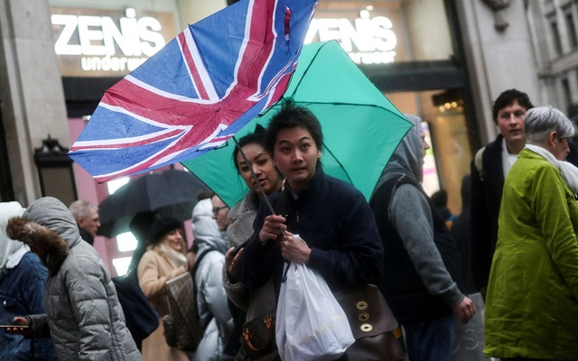 A pedestrian's Union flag umbrella is turned inside out by the wind at Oxford Street during Storm Dennis in London, Britain February 16, 2020. Reuters