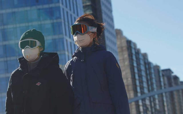 People wearing snow goggles and face masks are seen on a street, as the country is hit by an outbreak of the novel coronavirus, in Beijing's central business district, China Feb 16, 2020. REUTERS