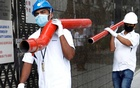 Construction workers wearing masks in precaution of the coronavirus outbreak carry pipes as they pass a building in the Central Business District in Singapore Feb 18, 2020. REUTERS