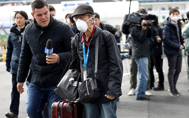 A member of the media approaches a passenger after he walked out from the cruise ship Diamond Princess at Daikoku Pier Cruise Terminal in Yokohama, south of Tokyo, Japan Feb 19, 2020. REUTERS