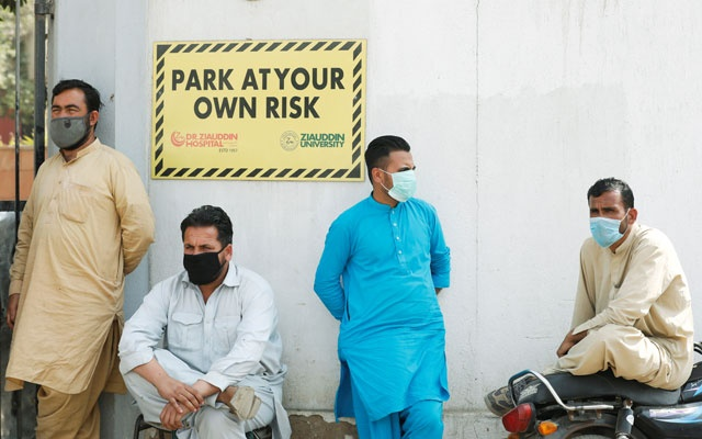 Men wearing face masks wait to see their relatives who were admitted after being affected from a suspected gas leak, at the hospital entrance in Karachi, Pakistan Feb 18, 2020. REUTERS
