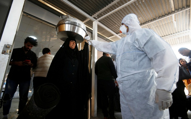 An Iraqi medical staff member checks a passenger's temperature, amid the new coronavirus outbreak, upon her arrival on the border between Iraq and Iran. REUTERS