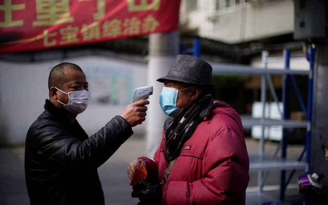 A man checks the temperature on a street in Qibao, an old river town on the outskirts of Shanghai, China, as the country is hit by an outbreak of the novel coronavirus, February 19, 2020. Picture taken February 19, 2020. REUTERS