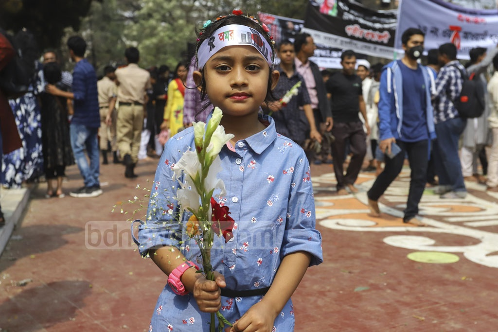 A child carrying flowers before placing them on the Central Shaheed Minar to pay respect to Language Movement martyrs on Friday. Photo: Asif Mahmud Ove