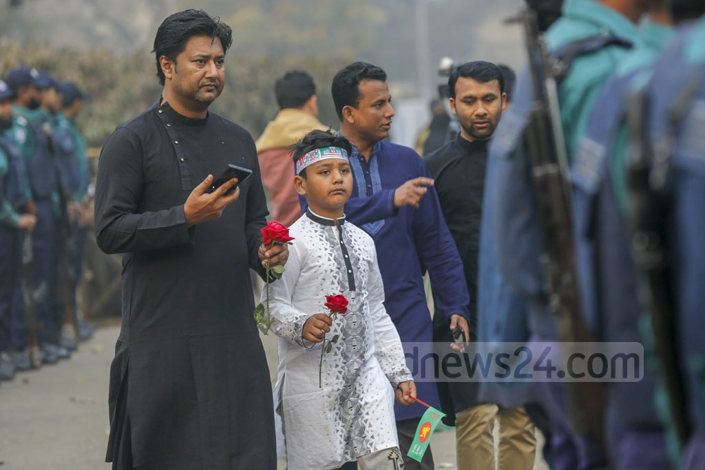 A child carrying flowers before placing them on the Central Shaheed Minar to pay respect to Language Movement martyrs on Friday. Photo: Mahmud Zaman Ovi