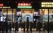 A train attendant waits to check passengers at the entrance of a nearly deserted railway station in Beijing, Feb 14, 2020. The New York Times