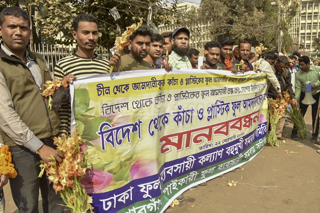 Flower traders form a human chain at Dhaka's Shahbag on Saturday demanding a ban on imports of natural and plastic flowers.