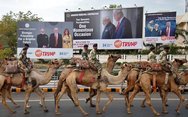 Border Security Force (BSF) soldiers ride their camels past hoardings with the images of India's Prime Minister Narendra Modi, US President Donald Trump and first lady Melania Trump, as they take part in a rehearsal for a road show ahead of Trump's visit, in Ahmedabad, India, Feb 21, 2020. REUTERS