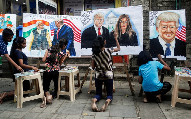 Students paint murals of US President Donald Trump and first lady Melania Trump on canvas sheets along a street in Mumbai, India, Feb 21, 2020. REUTERS