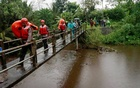 Rescue workers walk past a bridge as they search for students who were missing after a tidal surge swept them away during a school trip, in Sleman, Yogyakarta, Indonesia, Feb 21, 2020 in this photo taken by Antara Foto. Antara Foto/Andreas Fitri Atmoko/via REUTERS