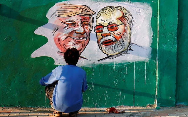 A man applies finishing touches to paintings of US President Donald Trump and India's Prime Minister Narendra Modi on a wall as part of a beautification along a route that Trump and Modi will be taking during Trump's upcoming visit, in Ahmedabad, India, Feb 17, 2020. REUTERS