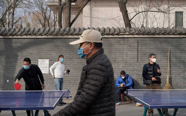 People wearing face masks play table tennis at a park, following an outbreak of the novel coronavirus in the country, in Beijing, China February 21, 2020. REUTERS