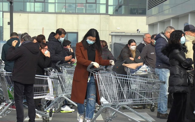A crowd of Italians wearing protective masks wait outside a closed supermarket in the town of Casalpusterlengo, one of the towns on lockdown due to coronavirus outbreak in Lombardy, in this still image taken from video in Casalpusterlengo, Italy, February 23, 2020. Local Team/REUTERS TV via REUTERS