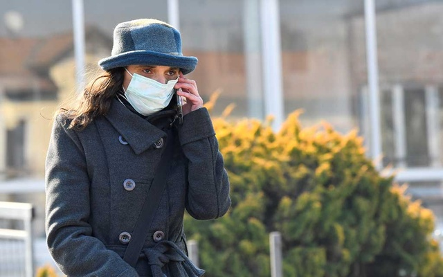 A woman wearing a face mask leaves the hospital of Codogno amid a coronavirus outbreak in northern Italy, in Codogno, Italy, Feb 22, 2020. REUTERS