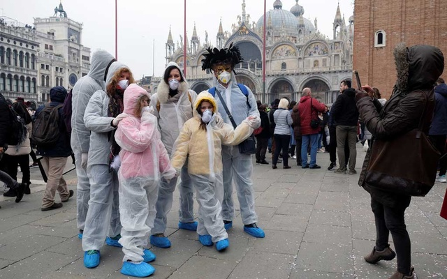 Carnival revellers wear protective face masks at Venice Carnival, which the last two days of, as well as Sunday night's festivities, have been cancelled because of an outbreak of coronavirus, in Venice, Italy February 23, 2020. Reuters