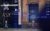 Pedestrians are reflected in a window in front of a board displaying stock prices at the Australian Securities Exchange (ASX) in Sydney, Australia, Feb 9, 2018. REUTERS