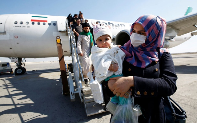 Passengers wearing protective masks disembark from a plane upon their arrival at Najaf airport, amid the new coronavirus outbreak, Iraq Feb 21, 2020. REUTERS