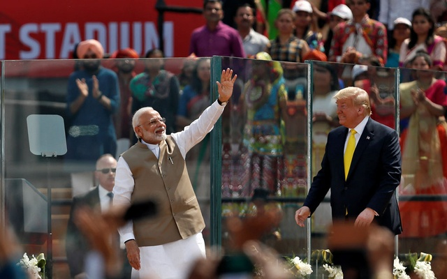India's Prime Minister Narendra Modi waves next to US President Donald Trump as they attend the