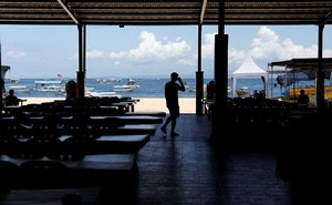 A worker walks at an empty waiting-room of a water sport attraction provider in Tanjung Benoa, Nusa Dua, Bali, Indonesia, February 6, 2020. Reuters