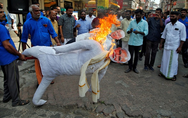 Supporters of Centre of India Trade Union (CITU) burn effigies depicting US President Donald Trump and India's Prime Minister Narendra Modi during a protest against Trump's visit to India, in Kochi, India, Feb 24, 2020. REUTERS