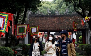 Tourists wear protective masks while they visit Van Mieu or Temple of Literature in Hanoi, Vietnam February 6, 2020. Reuters