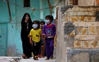 Iraqi children wear protective masks as they walk near a religious school where the first coronavirus case was detected, following the outbreak of the new coronavirus, in the holy city of Najaf, Iraq Feb 24, 2020. REUTERS