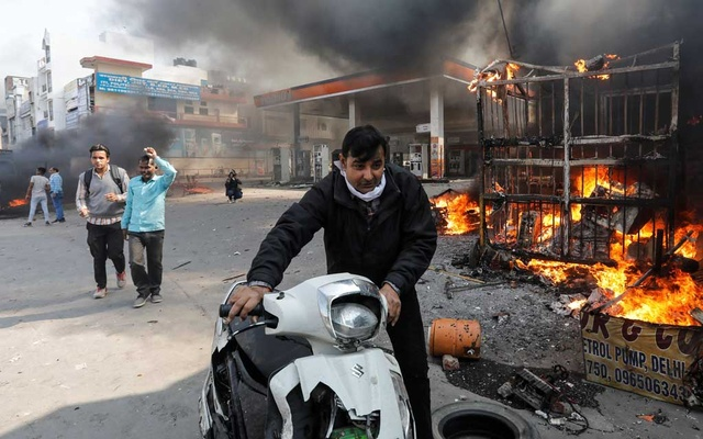 A man pushes his damaged scooter past a burning petrol pump during a clash between people supporting a new citizenship law and those opposing it, in New Delhi India, February 24, 2020. Reuters