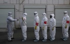 Volunteers in protective suits are being disinfected in a line in Wuhan, the epicentre of the novel coronavirus outbreak, in Hubei. REUTERS