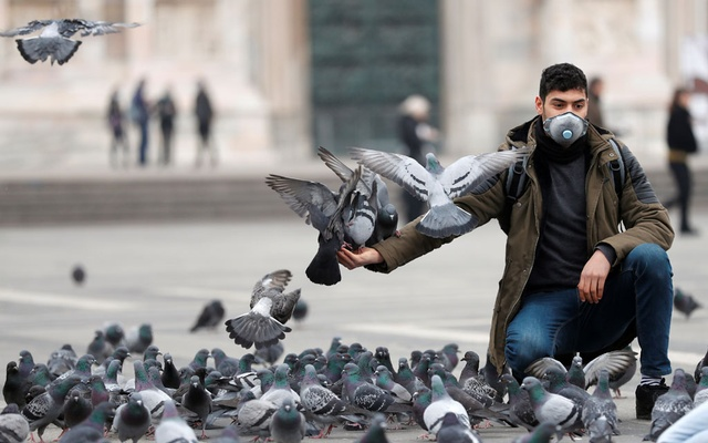 A man in a face mask feeds pigeons in Milan, as the country is hit by the coronavirus outbreak, Italy Feb 25, 2020. REUTERS