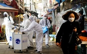 A woman wearing a mask to prevent contracting the coronavirus reacts as employees from a disinfection service company sanitize a traditional market in Seoul, South Korea, Feb 26, 2020. REUTERS