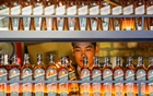 A bartender takes a bottle of Johnnie Walker whisky at Barmaglot bar in Almaty, Kazakhstan Jun 22, 2017. REUTERS