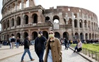 People wearing protective masks walk past the Colosseum in Rome, Italy, February 25, 2020. Reuters