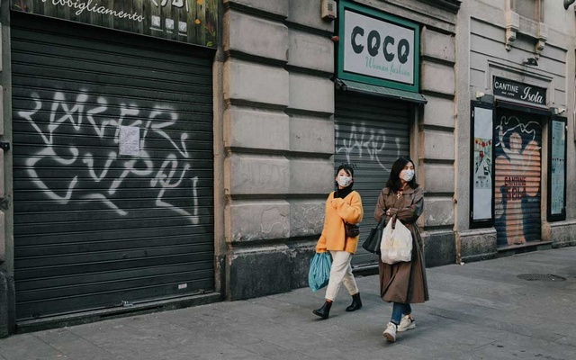 People in masks walk past closed shops in Milan on Feb. 23, 2020. The spread of the deadly epidemic to Europe's fourth-largest economy has heightened fears of disruption in the global supply chain. (Andrea Mantovani for/The New York Times)