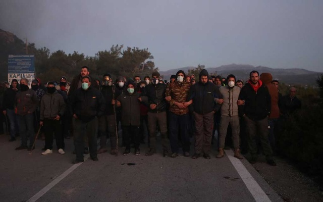 Locals, who oppose the building of a new closed migrant detention centre, block the road to riot police, in Karava on the island of Lesbos, Greece, Feb 25, 2020. REUTERS