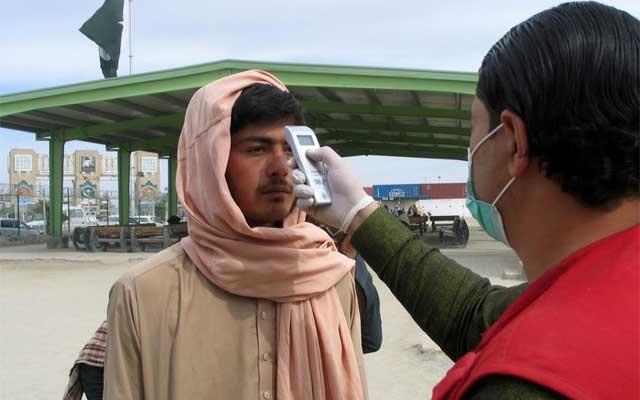 A health worker takes the temperature of a man, who returned from Afghanistan, for a medical observation as a preventive measure following the coronavirus outbreak, near the Friendship Gate, crossing point at the Pakistan-Afghanistan border town of Chaman. REUTERS