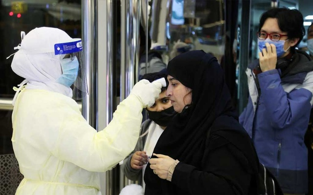 Passengers coming from China wearing masks to prevent a new coronavirus are checked by Saudi Health Ministry employees upon their arrival at King Khalid International Airport, in Riyadh, Saudi Arabia Jan 29, 2020. REUTERS